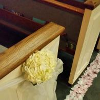 White hydrangea pew bow with pink and white silk petal runners