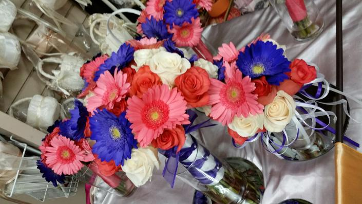 Coral and purple gerbera daisies with coral roses