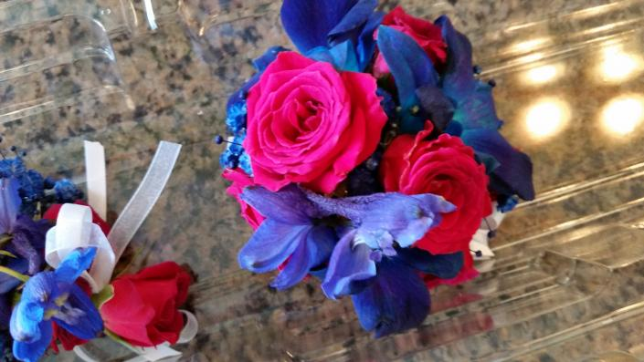 Blue delphinium and hot pink spray roses corsage