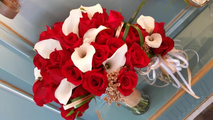Red roses and white mini callas with a touch of gold baby's  breath  wrapped in gold satin